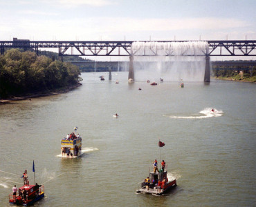 The 2001 Sourdough Raft Race, passing beneath the High Level Bridge's Great Divide waterfall during Klondike Days.